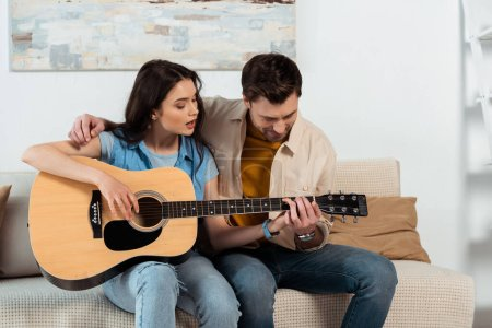 Photo for Man teaching girlfriend to playing acoustic guitar in living room - Royalty Free Image