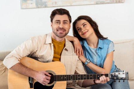 Photo pour Beau homme souriant à la caméra tout en jouant de la guitare acoustique près de petite amie - image libre de droit