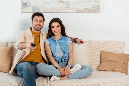 Photo pour Couple souriant regardant la caméra tout en regardant la télévision à la maison - image libre de droit