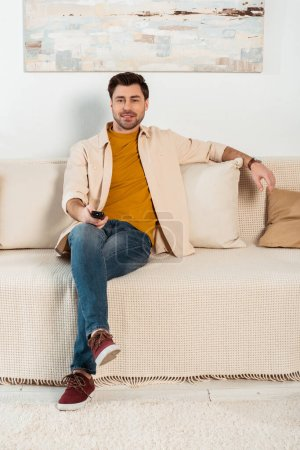 Photo for Handsome man holding remote controller and smiling at camera on sofa - Royalty Free Image
