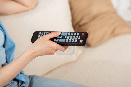 Photo pour Vue recadrée de la fille tenant télécommande sur le canapé - image libre de droit