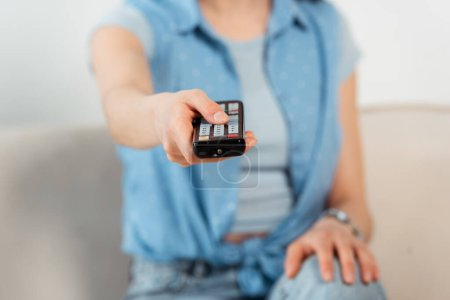 Selective focus of young woman clicking channels on couch
