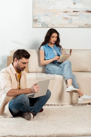 Man using laptop near woman reading book in living room