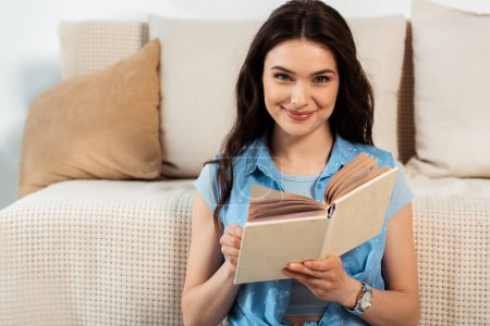 Young woman smiling at camera while reading book in living room