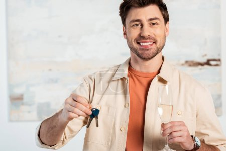 Photo for Smiling man looking at camera while holding keys of new house and glass of champagne - Royalty Free Image