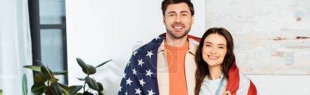 Panoramablick auf lächelndes Paar, das sich in amerikanische Flagge hüllt und in die Kamera blickt