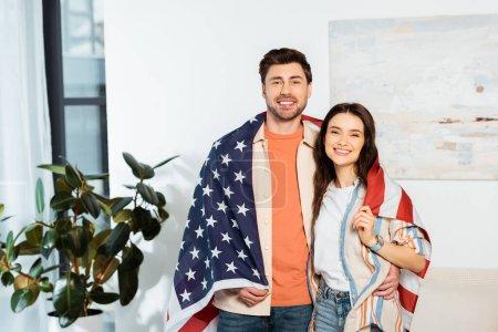 Schöner Mann umarmt lächelnde Freundin, während er sich in amerikanische Flagge hüllt