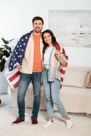 Photo pour Jeune couple enveloppant dans le drapeau américain souriant à la caméra dans le salon - image libre de droit
