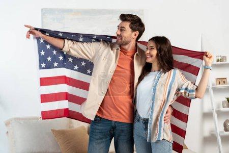 Photo pour Homme souriant pointant du doigt et embrassant sa petite amie tout en tenant le drapeau américain à la maison - image libre de droit