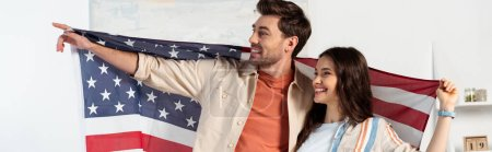 Panoramic crop of smiling man pointing with finger while holding with girlfriend american flag