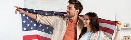 Panoramaausschnitt eines lächelnden Mannes, der mit dem Finger zeigt, während er mit Freundin amerikanische Flagge hält