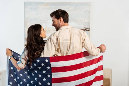 Back view of young couple smiling at each other while holding american flag at home
