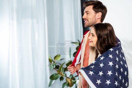 Photo pour Vue latérale du couple souriant dans le drapeau américain regardant loin à la maison - image libre de droit