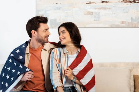 Photo pour Jeune couple enveloppé dans un drapeau américain souriant à la maison - image libre de droit