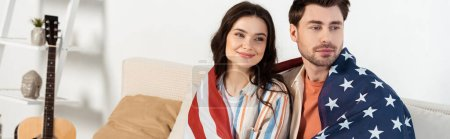 Panoramic shot of smiling woman wrapped in american flag sitting near boyfriend on couch