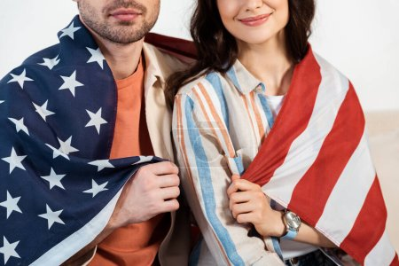 Cropped view of smiling woman wrapped in american flag sitting near boyfriend