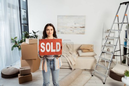 Attractive girl holding nameplate with sold lettering near carton boxes and ladder in living room