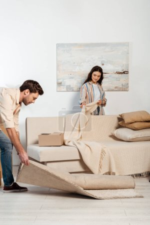 Selective focus of woman holding plaid near couch while boyfriend turning off carpet in living room