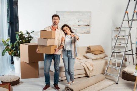 Photo pour Femme positive tenant les clés de la nouvelle maison près du petit ami avec des boîtes en carton dans le salon - image libre de droit