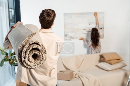 Photo for Back view of man holding carpet while girlfriend taking painting from wall during moving - Royalty Free Image