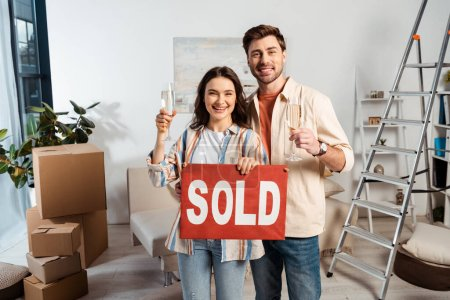 Photo pour Couple souriant avec verres de champagne tenant plaque signalétique avec lettrage vendu pendant le déménagement dans le salon - image libre de droit