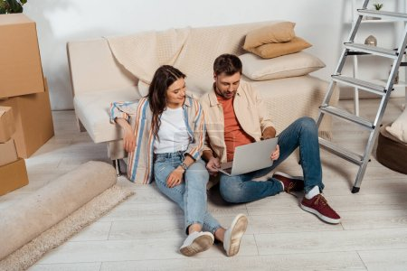 Photo pour Femme souriante assise près du petit ami en utilisant un ordinateur portable dans une nouvelle maison - image libre de droit