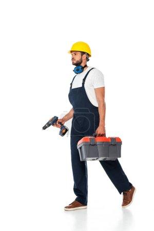 Photo pour Beau travailleur en salopette et casque dur tenant boîte à outils et tournevis électrique tout en marchant sur fond blanc - image libre de droit