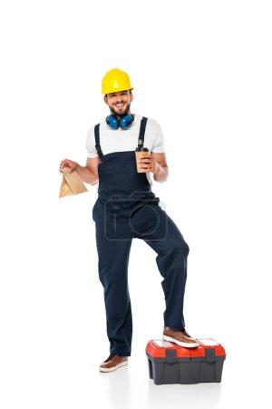 Photo pour Réparateur souriant en uniforme tenant sac en papier et tasse jetable près de la boîte à outils sur fond blanc - image libre de droit
