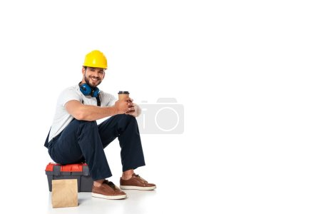 Smiling repairman in uniform holding coffee to go while sitting on toolbox near paper bag on white background