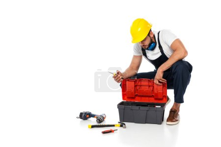 Photo for Workman in hardhat and ear defenders holding screwdriver near tools and toolbox on white background - Royalty Free Image