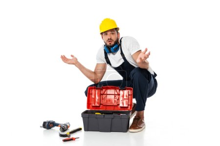 Photo for Confused workman showing shrug gesture near tools and toolbox on on white background - Royalty Free Image