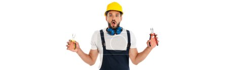 Photo for Panoramic shot of shocked repairman in uniform holding pliers isolated on white - Royalty Free Image