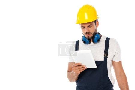 Photo pour Ouvrier en casque et protège-oreilles tenant la tablette numérique isolée sur blanc - image libre de droit