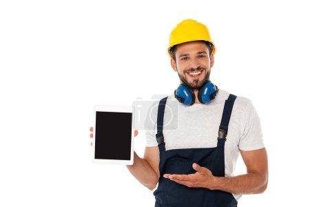 Photo pour Travailleur manuel souriant pointant de la main vers la tablette numérique avec écran blanc isolé sur blanc - image libre de droit