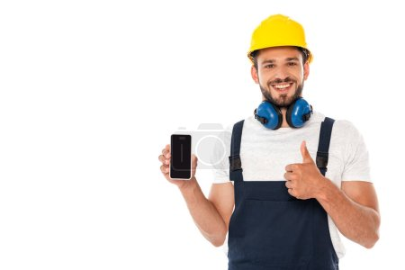 Smiling handyman in workwear showing like gesture while holding smartphone with blank screen isolated on white