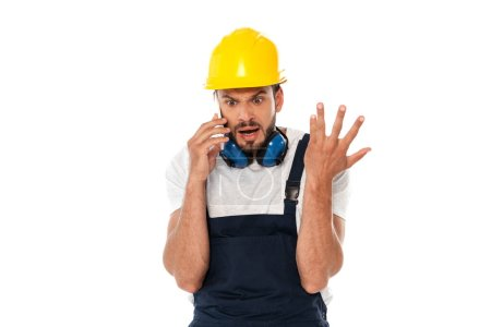 Angry workman gesturing while talking on smartphone isolated on white