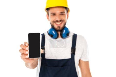 Photo pour Mise au point sélective de l'ouvrier souriant montrant smartphone avec écran blanc isolé sur blanc - image libre de droit