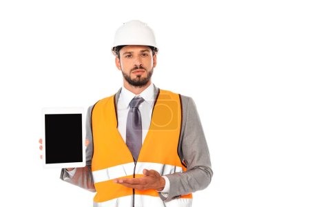 Photo for Engineer in suit and safety helmet pointing with hand at digital tablet isolated on white - Royalty Free Image