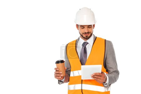 Photo for Handsome engineer in suit and hardhat holding coffee to go and digital tablet isolated on white - Royalty Free Image