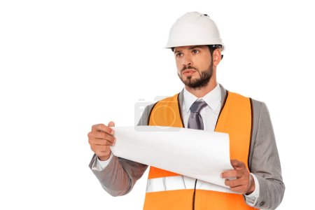 Handsome engineer in suit and hardhat holding blueprint and looking away isolated on white