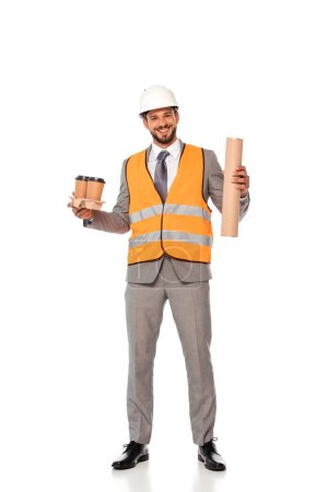 Photo for Smiling engineer in suit and safety vest holding paper cups and blueprint tube on white background - Royalty Free Image