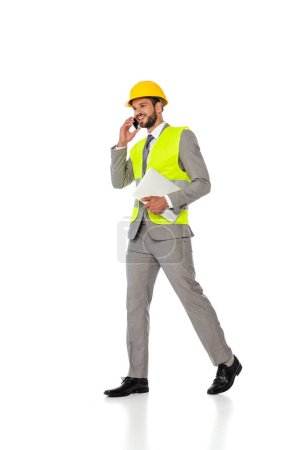 Smiling engineer in hardhat and suit talking on smartphone and holding laptop on white background