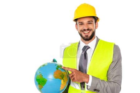 Photo pour Ingénieur en casque et gilet de sécurité pointant du doigt le globe et souriant à la caméra isolée sur blanc - image libre de droit