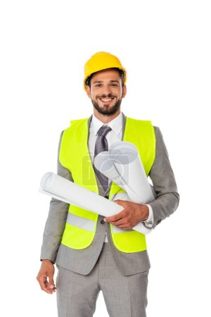 Photo pour Bel ingénieur positif en costume et gilet de sécurité tenant des plans et regardant la caméra isolée sur blanc - image libre de droit