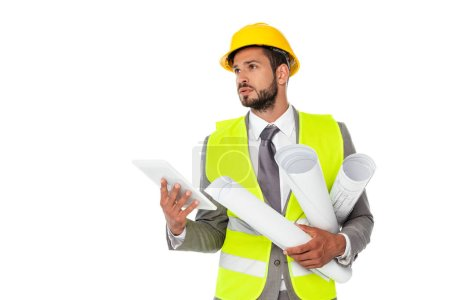 Photo for Handsome engineer holding blueprints and digital tablet while looking away isolated on white - Royalty Free Image