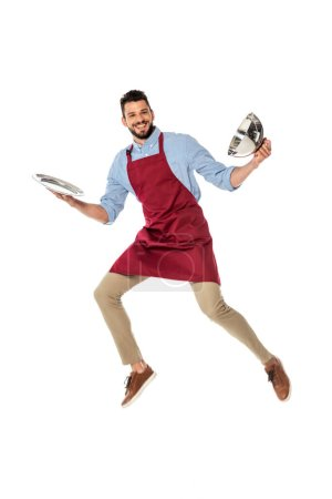 Photo for Positive waiter in apron holding tray and dish cover while jumping isolated on white - Royalty Free Image