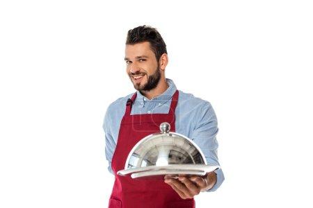 Selektiver Fokus des gut aussehenden lächelnden Kellners, der Tablett und Tellerdecke isoliert auf Weiß hält
