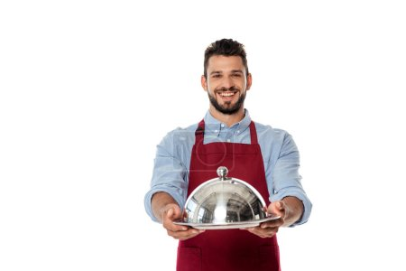 Lächelnder Kellner in Schürze zeigt Metalltablett und Tellerdeckel isoliert auf weiß