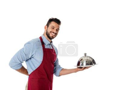 Kellner in Schürze mit Metallschale und Tablett, während er isoliert auf weiß in die Kamera lächelt