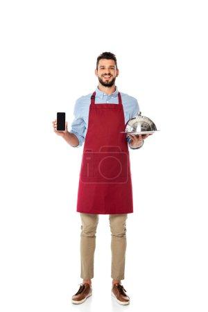 Schöner lächelnder Kellner mit Smartphone mit leerem Bildschirm und Tablett mit Geschirrdeckel auf weißem Hintergrund
